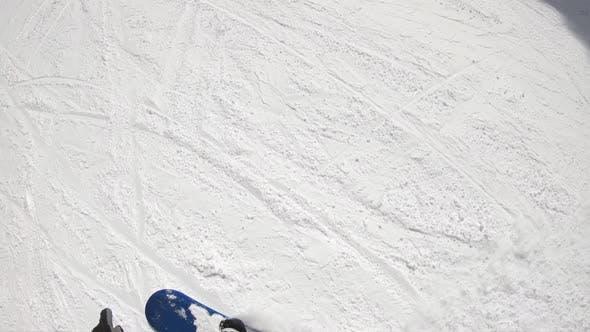 POV of a snowboarder snowboarding downhill at a ski resort.