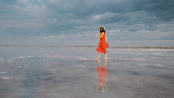 Thumbnail for Young Woman Tourist in a Waving Dress Walks Along a Salt Lake in Which the Sky Is Reflected