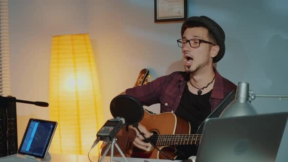 Thumbnail for Cheerful Young Musician Playing the Guitar and Singing Into Microphone in Home Studio