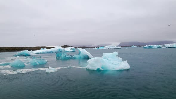 Majestic Drone Shot of Icebergs Scattered in the Blue Ocean Iceland