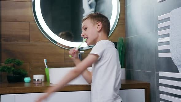10-Aged Light Haired Boy in Homewear Dancing During Cleaning His Teeth in Front of Mirror