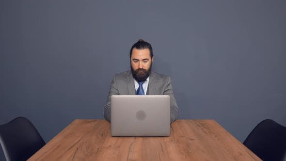 Bearded Businessman Is Working On Laptop Sitting at Office Desk