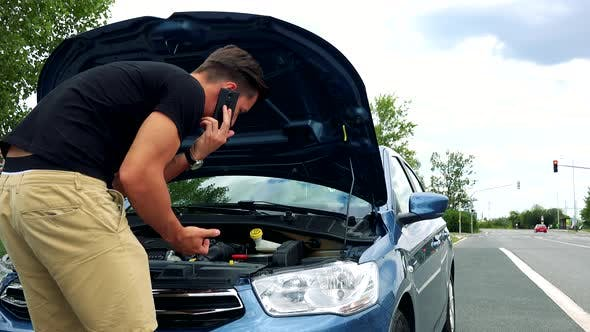 Thumbnail for Young Handsome Man Looks on Engine in Car and Phone with Smartphone - Accident