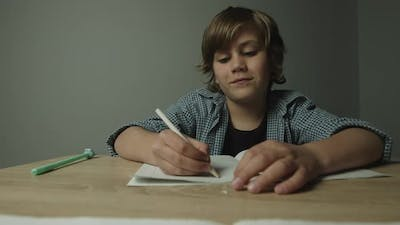 Young Cute Boy Sits at Desk Writes Homework Starts to Smile and Laugh While Writing Down in Notebook