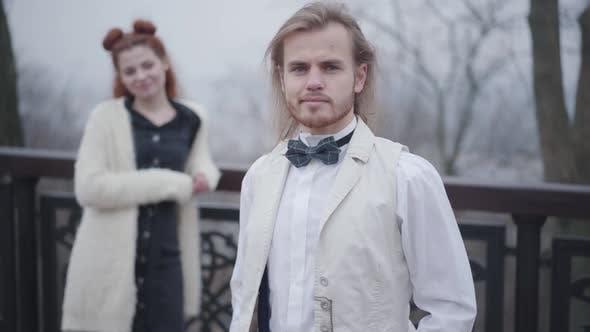 Thumbnail for Handsome junge kaukasische Mann in retro Kleidung Blick zurück auf seine hübsche Freundin, Drehen zu
