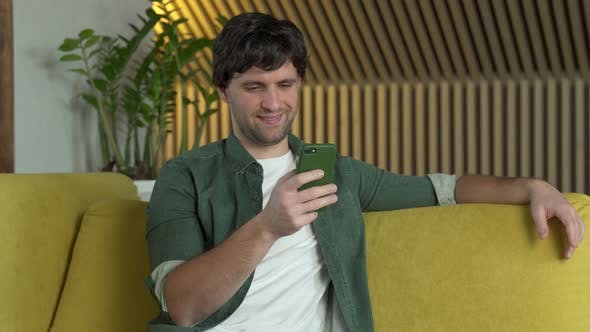 Young Man in a Green Shirt Uses a Smartphone at Home on a Yellow Sofa