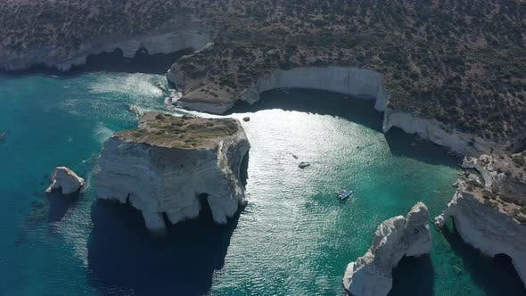 Thumbnail for Aerial Wide Establishing Shot of Tropical Bay in Greece with White Rocks and Boats in the Ocean