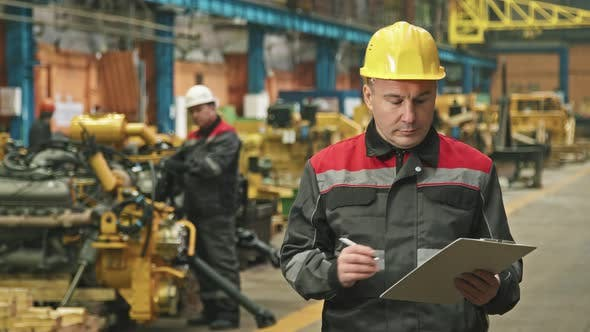 Portrait Of Serious Foreman At Tractor Plant