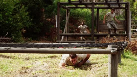 Military people crawling under the hurdles during obstacle course 4k