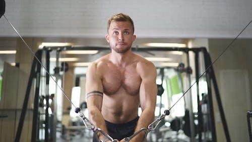 Bodybuilder trainieren auf dem Simulator im Fitnessstudio