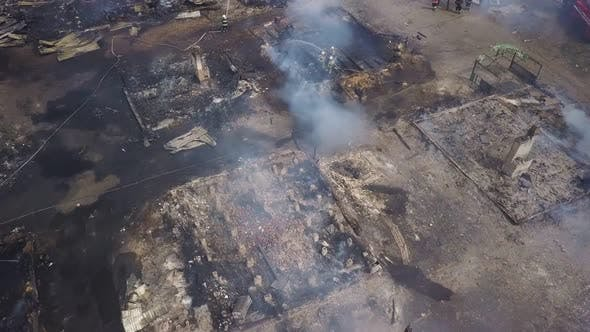 Aerial View Over Smouldering Ruins in Smoke, Firefighters Are Extinguishing Fire