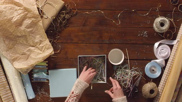 Thumbnail for Woman Packing Mug into Gift Box Filled with Craft Paper