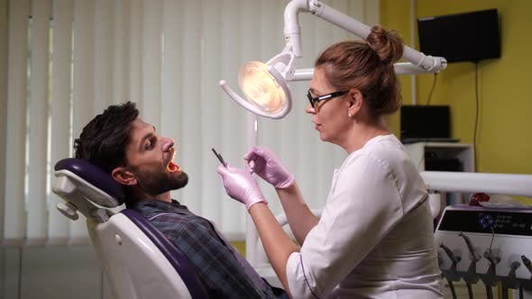 Thumbnail for Woman Dentist Examining Patient's Teeth in Clinic