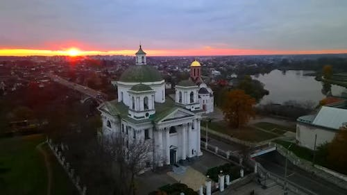 The Camera Circles Around a Small Church on the River Bank in a Small European City at Bright Sunset