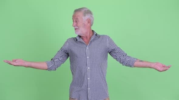 Thumbnail for Happy Senior Bearded Man Comparing Something