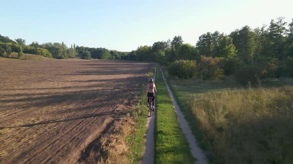 Aerial Shot of Young Sport Woman Rides Bicycle on Countryside Road at Summer Sunset. Happy Holiday