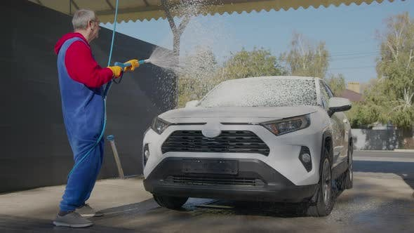 Thumbnail for Elderly Man Washes His Car with Foam and Water