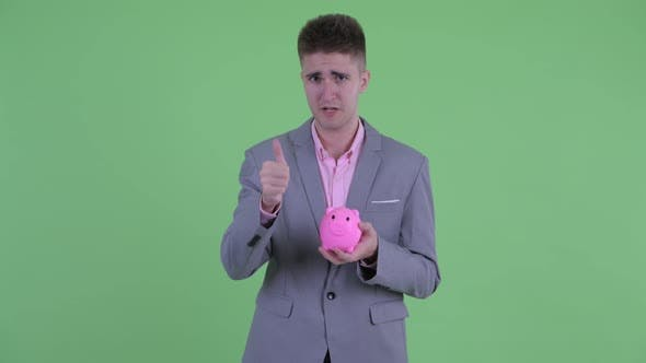 Thumbnail for Happy Young Businessman Holding Piggy Bank and Giving Thumbs Up