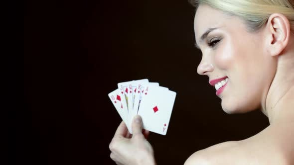 Young woman holding hand on cards and winking
