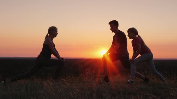 Cover Image for Family with a Child Doing Exercises Together in a Picturesque Place at Sunset