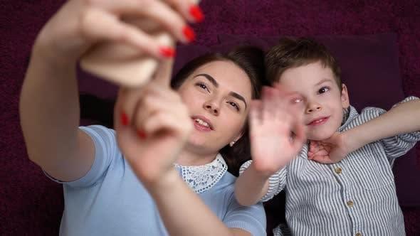 Mutter und ihr Sohn machen einen Selfie oder Video anruf zum Vater oder Verwandten auf dem Teppich.
