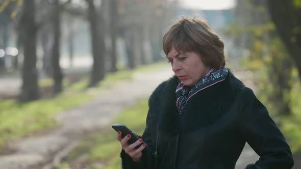 Thumbnail for Smart Blonde Woman in Stylish Coat Texting on Smartphone on a Street in Autumn
