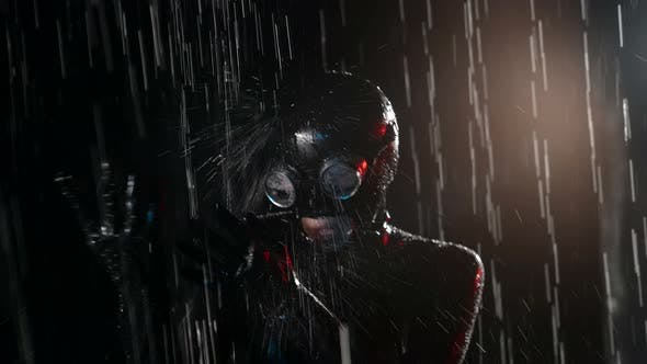 Woman in Latex Suit and Mask is Standing Under Water Flow in Studio Silhouette in Darkness