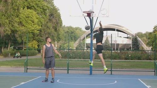 Junger Mann Werfen Basketball-Ball in Hoop auf Platz im Park erfolgreich. Sportsman Üben