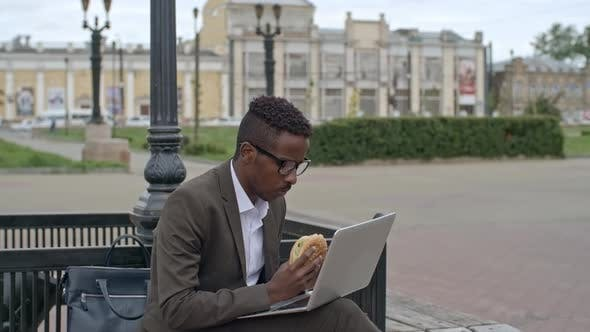 Thumbnail for Businessman Using Laptop Outdoor and Eating Burger