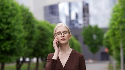 Serious Business Woman Talking on the Phone in the Street