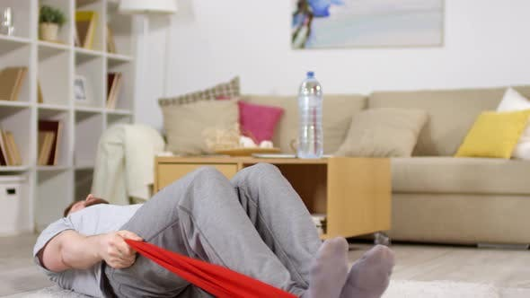 Thumbnail for Man Doing Sit Ups with Resistance Band during At-Home Workout