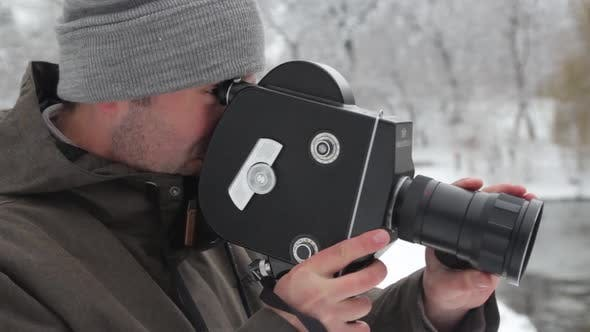 A Male Cameraman Shoots Video on an Old Vintage Camera Krasnogorsk in the Park in Winter. Kyiv