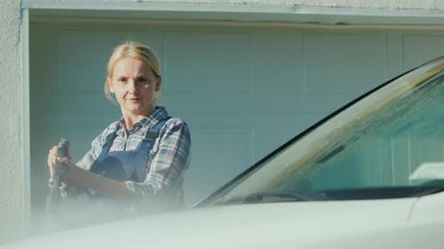 A Woman Washing My Car in the Backyard of Her House on the Background of the Doors To the Garage