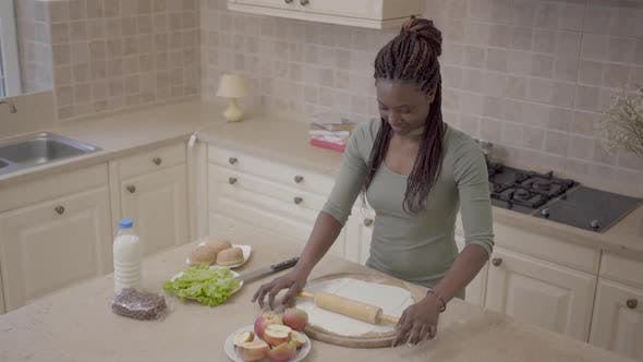 Cover Image for Beautiful Smiling African American Woman Rolling Dough with Rolling Pin for Apple Pie on the Modern