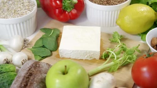 Appetizing Feta Cheese on a Wooden Board Surrounded By Many Different Vegetables