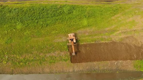 Excavator Digging a Trench in the Field