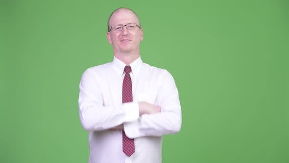 Thumbnail for Mature Bald Businessman with Arms Crossed