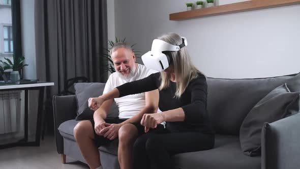 Elderly Couple Is Relaxing on the Sofa in the Living Room an Adult Woman in Virtual Reality Glasses