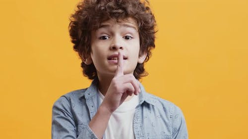 Its Our Secret. Cute Curly Boy Putting Finger on His Lips, Showing Be Quiet and Keep Silence Gesture