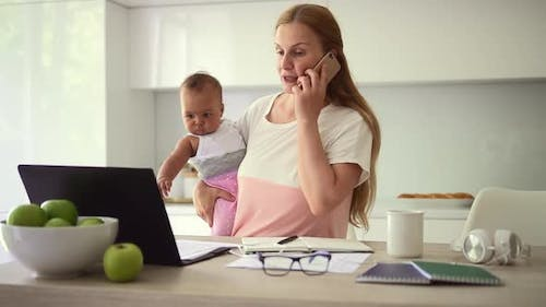 Woman Talking on Phone and Holding Little Baby Standing in Home Room Spbd