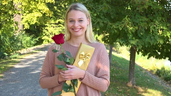 A Young Beautiful Woman Holds a Rose and a Present and Smiles Happily at the Camera in a Park