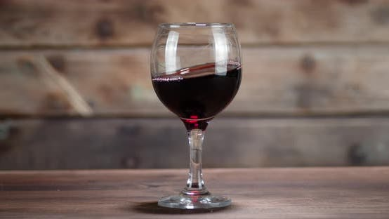 Thumbnail for Red Wine Moves in a Glass on the Table.