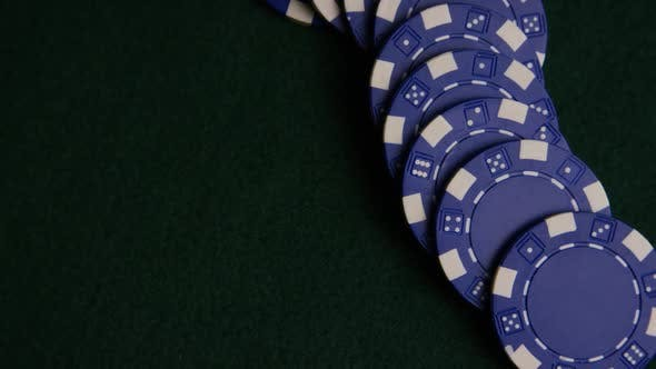 Rotating shot of poker cards and poker chips on a green felt surface - POKER 051