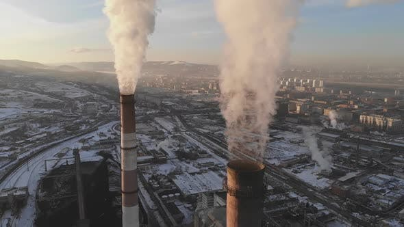 Aerial view of smoke rising from the chimney of a coal boiler. Slow motion, top view