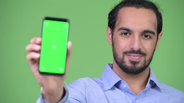 Thumbnail for Young Happy Bearded Indian Businessman Showing Phone
