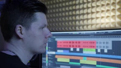 Sound engineer at music computer monitor and mixing console