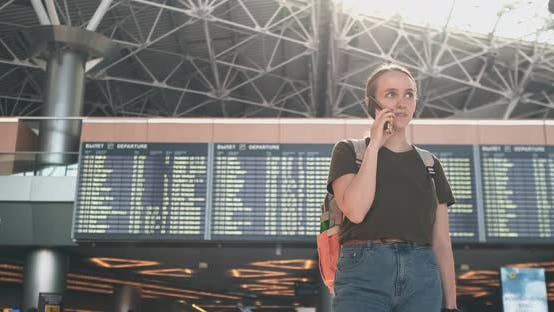 Thumbnail for Girl Traveler at the Airport To Talk on a Mobile Phone