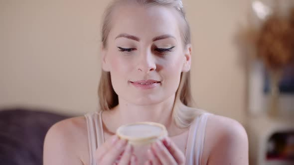 Cover Image for Atractive Woman Blowing in Makeup Powder and Smile Into Camera Cosmology Concept