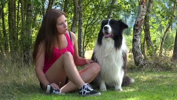 Thumbnail for A Young Beautiful Woman and a Border Collie Sit in a Meadow, the Woman Pets and Talks To the Dog
