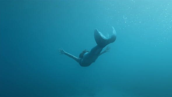 Mermaid in the depths of the ocean water